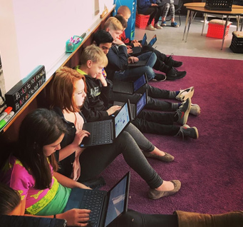 students using laptops on the floor