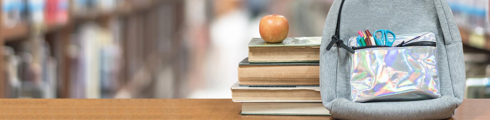 Stack of books with apple and backpack
