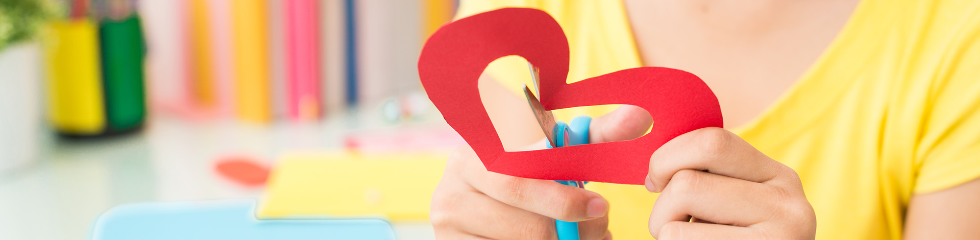 Student cutting out paper heart