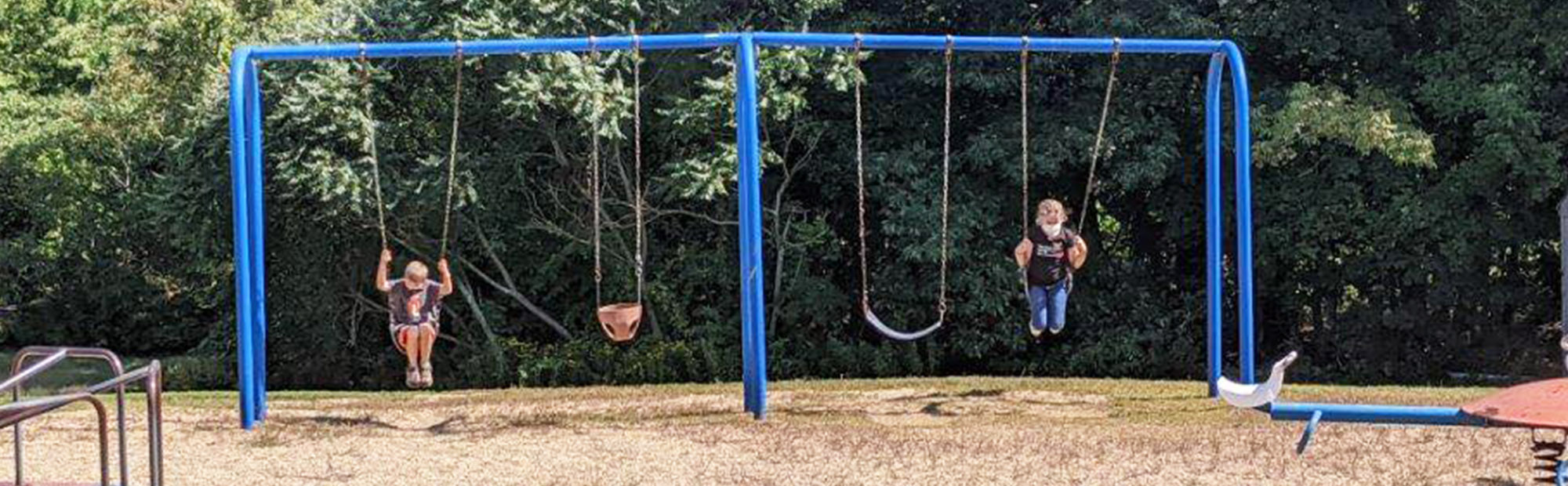 Students enjoying the swings on the school playground