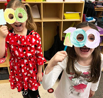 Two spirited elementary girls with 100-day paper eye glasses