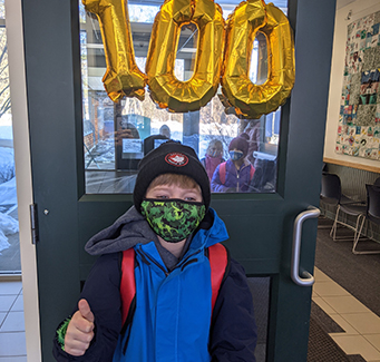 Spirited student posing for a picture in front of 100 Days of School Sign