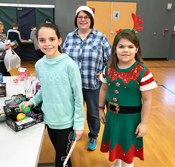 Students with adult attending a holiday event in the school gym