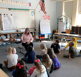 Teacher reading with her students in the classroom