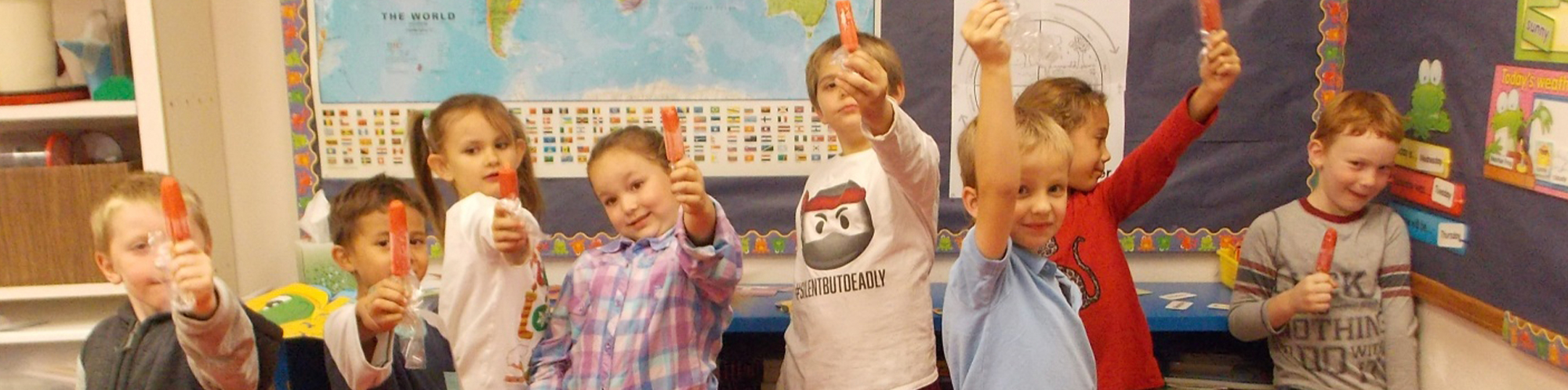 Young students holding up popsicles