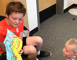 Older student reading book to young student