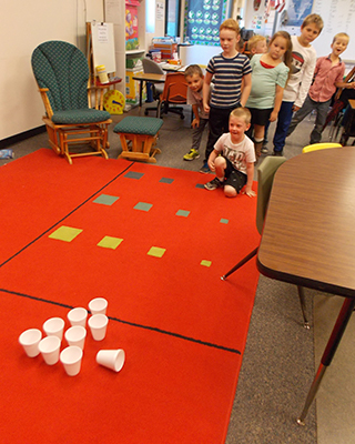 Students playing game with cups