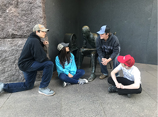 Students sitting with statues
