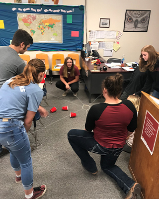 Students playing game with cups and string