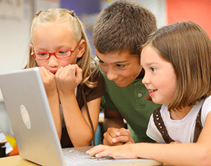three elementary students hudled around a laptop