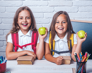 two students holding apples and sitting with backpacks on