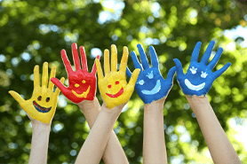 group of hands painted with smiley faces