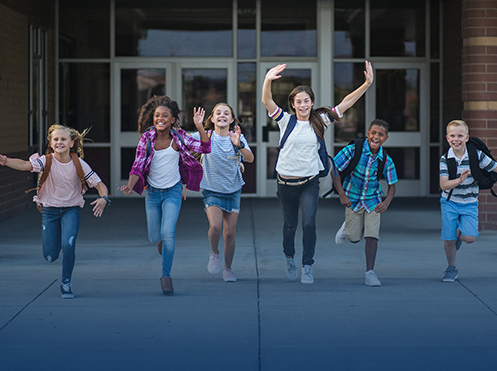 students running with backpacks in front of a school