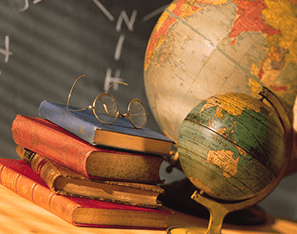 a couple of globes next to a stack of books with a pair of glasses sitting on top