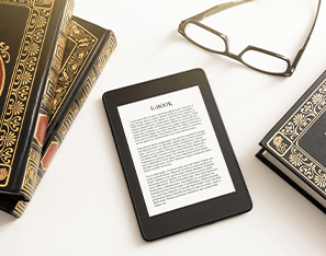 e-reader sitting next to books and a pair of glasses