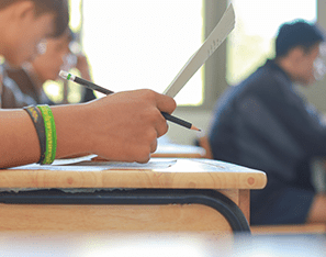 students filling out paperwork at desks