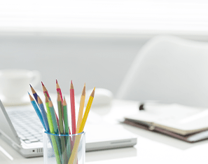 Colored pencils, laptop, and notebook sitting on a desk