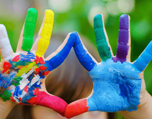 pair of hands covered in rainbow colored fingerpaints
