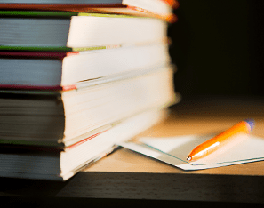 stack of books next to a notebook and pencil