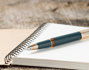 blank notebook with a pen sitting on top