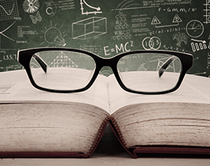 reading glasses sitting on top of a book by a chalkboard