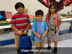 view more photos of students receiving backpacks and supplies