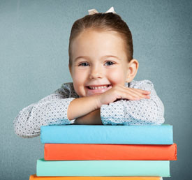 smiling student with a stack of books