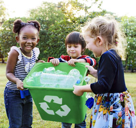 students holding a recycling bin