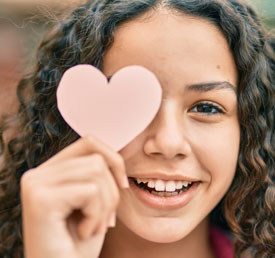 student holding a heart shaped piece of paper