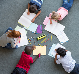 students doing classwork on the floor
