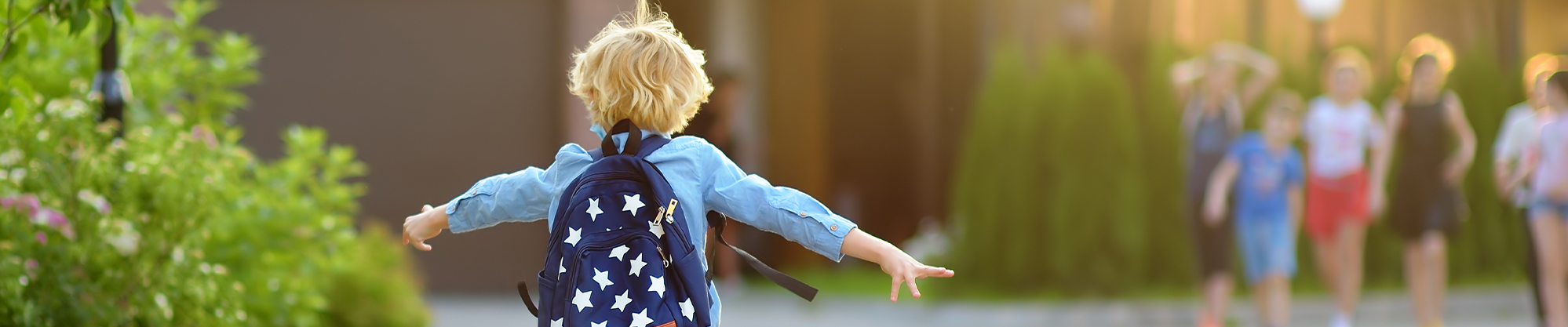Student with backpack happily running towards school