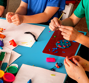 Students working with crafts at a classroom table