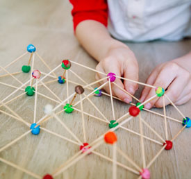 student building a structure with toothpicks