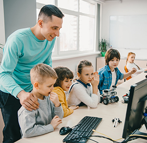 teacher helping students at computers