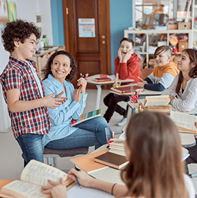 teacher and group of students with boy sharing in front of class