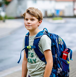 young male student with blue backpack