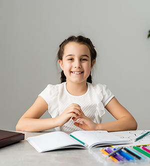 girl at a desk with school supplies