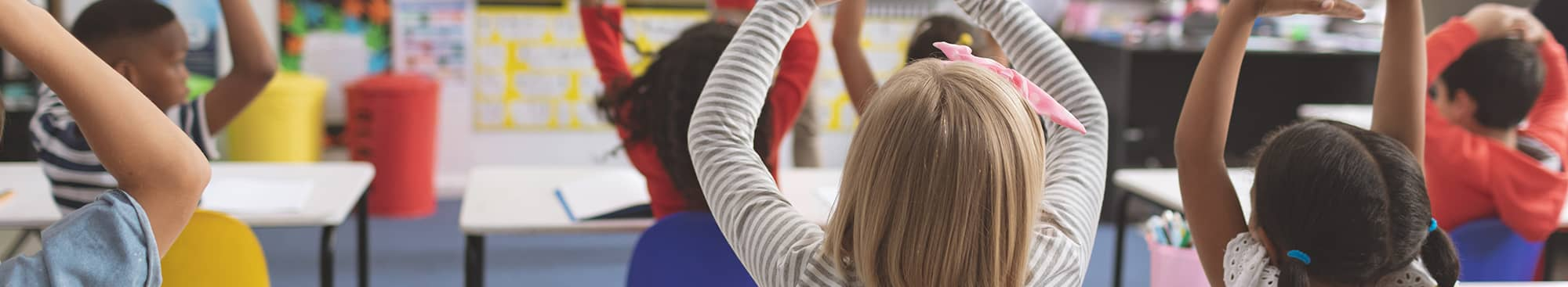 Students Stretching Arms to the Sky in a Classroom