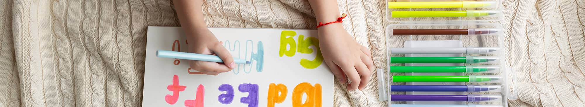 Child Coloring Alphabet Letters with Bright Markers