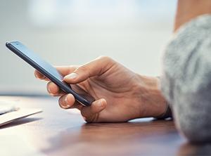 Woman holding phone on desk