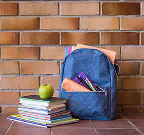 backpack with school supplies and stack of books