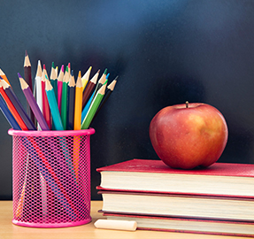 colored pencils and books with apple on it