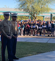 Two veterans outside with students in the background