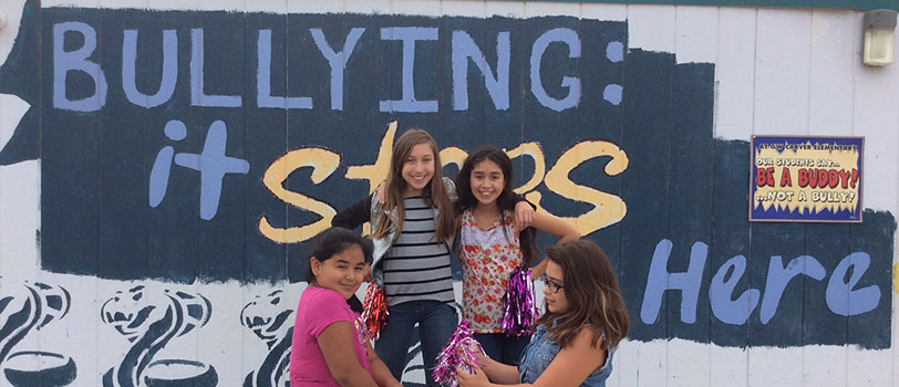 Students pose in front of a sign reading bullying: it stops here