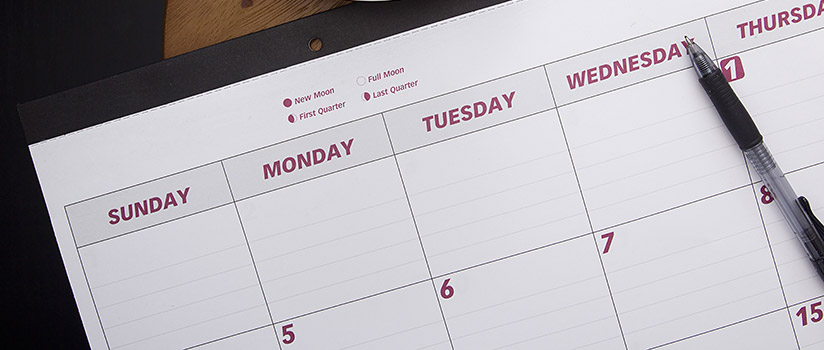 Calendar with a pen on top of it