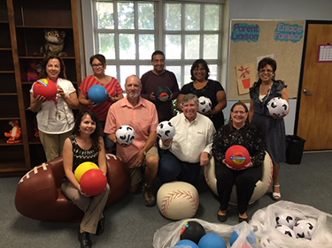 Sunrise Rotary Club members pose with sports balls
