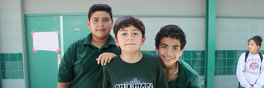 Three boys pose outside