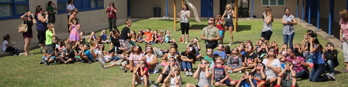 Students and teachers outside watching the eclipse with eclipse glasses