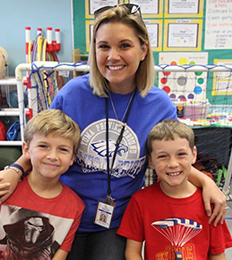 teacher smiling with two students in a classroom