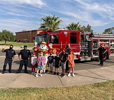 Kids posing with firefighters, firetruck, and Dalmatian mascot